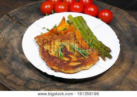 Cutlet with potato wedges tomatoes green asparagus garnished with parsley and rosemary