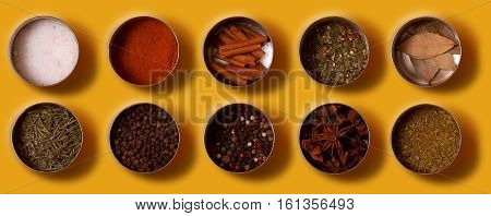 Bright set of spices Asian and South American cuisine in metal cans on yellow background