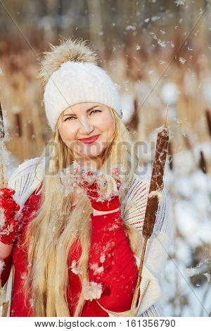 Smiling woman stands on frozen pond among flying reeds fluff.