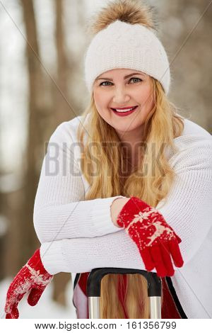 Young smiling woman stands leaning on handle of trolley bag in winter park.