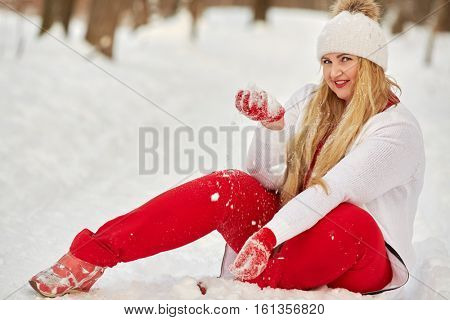 Young smiling woman sits on snow, holding handful of snow in hand.