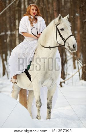Young woman in white dress and white fur mantle on white horse in park.