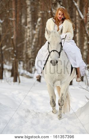 Young woman in white dress and white fur mantle rides on white horse in park.