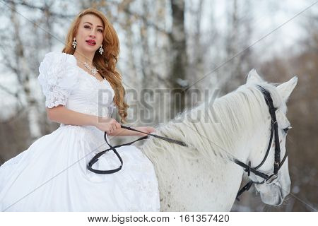 Young woman in white dress rides on white horse in park.