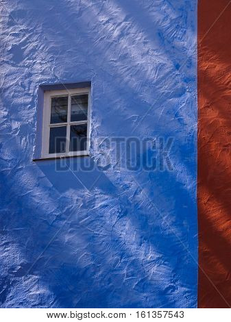 Colourful wall facade with window and shadows from sidelighting at Portmeirion Wales