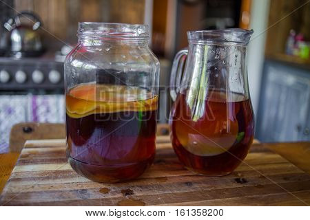 Close up image of the step by step of how to make kombucha in an actual kitchen with a real kombucha scobie or bacterial culture and black tea