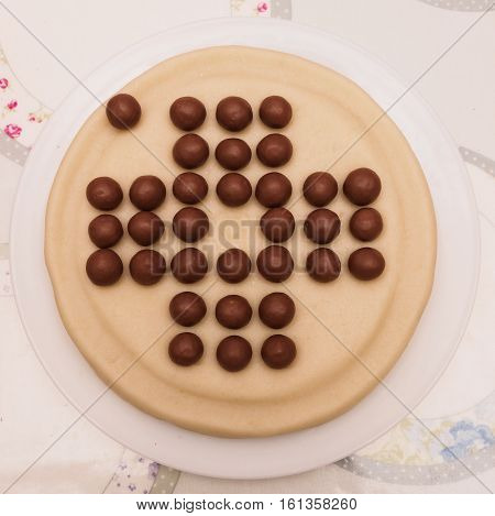 Bespoke cake in the stye of a solitaire board with marzipan and chocolate covered malt honeycombe spheres.