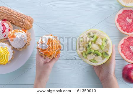 Hands of a young woman holding a cake and fruit salad making a choice between them. Woman making a choice between sweets and fruits. Healthy vs unhealthy food. top view flat lay.