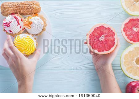 Hands of a young woman holding a grapefruit. Woman making a choice between cake and fruits made a choice in favor of fruits and holding half a grapefruit. Unhealthy vs healthy food top view.