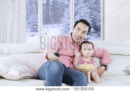Happy father holding remote control while watching tv with his daughter winter background on the window