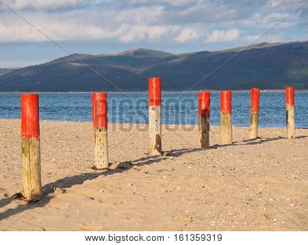 Colourful marker posts and estuary at Ynyslas at the head of the Dyfi (Dovey) estuary just north of Borth Ceredigion Wales.