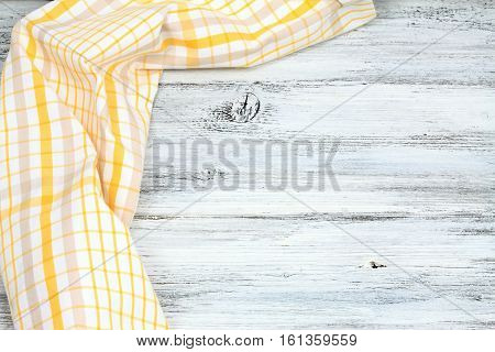 Dish cloth in yellow and white on wooden table. Linen tea towel on board good for background