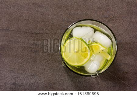 alcoholic cocktail with green lemon and ice closeup top view