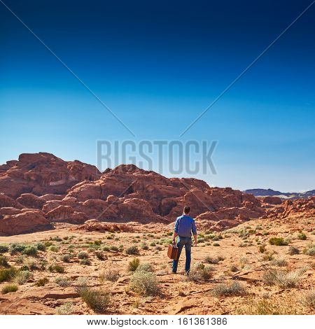 lone man with suitcase standing in desert alone