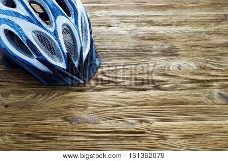 Bicycle helmet on wooden background with copy space.