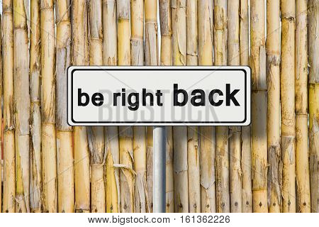 Be right back written on road sign against a bamboo fence - concept image
