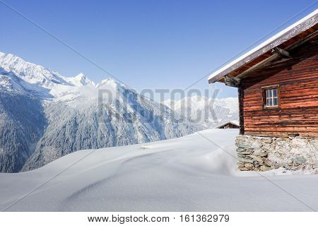 wooden hut in the snowy austrian alps