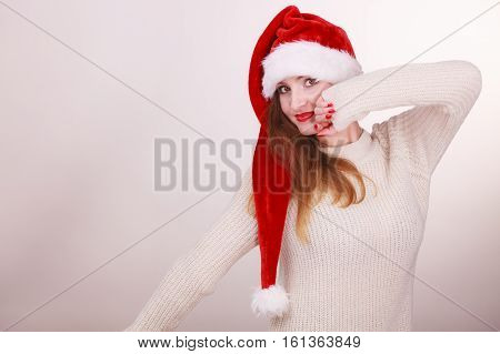 Beautiful girl wearing christmas cap. Young woman cheering in santa hat. Celebration fashion costume relax concept.