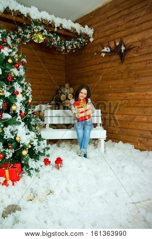 Happy girl glad Christmas gifts sitting near Christmas tree elegant