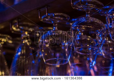 Glasses for cognac and cocktails hang on the shelf at restaurant. On them blue yellow and pink reflection of light from interior illumination of restaurant which create the atmosphere of a night club party.