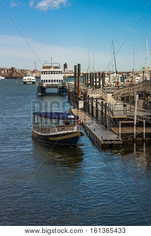 Boston USA - April 28 2015: Pier of Boston Wharf with sail boat and Charles River Boston Massachusetts the United States. People on the background
