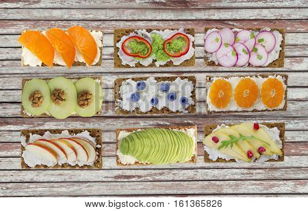 Sandwiches with cream cheese and fresh berries fruits and vegetables. Fresh healthy appetizer snack with crispbread.