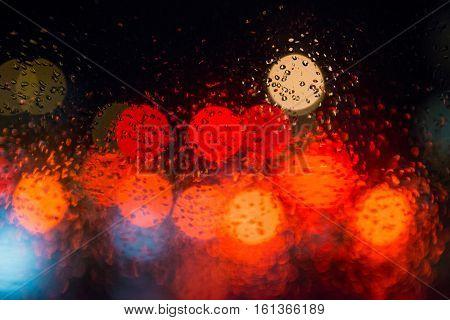 Rain drops on window with street bokeh lights, colorful street lights