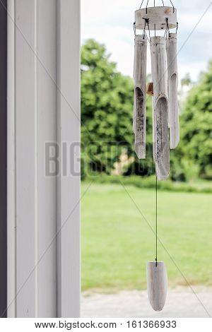 white wooden wind chime with green plants