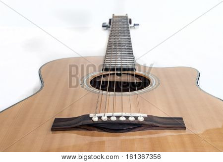 Wooden Acoustic Guitar Seen From Button Over White Background