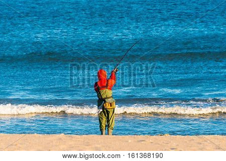 A fisherman casting his line into blue ocean water on a cold wintry day