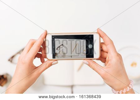 Modern technology. Nice pleasant woman wearing a bracelet and holding a smartphone while taking photo of her workplace