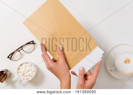 Morning post. Nice pleasant woman holding paper envelope and putting sheets of paper into it while sending letters