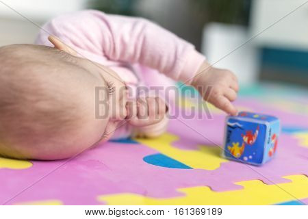 adorable baby lying on Child-friendly floor mats puzzle and suck his thumb