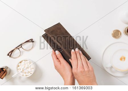 Keep your money safe. Pleasant nice woman holding a wallet and opening it while wanting to take out money