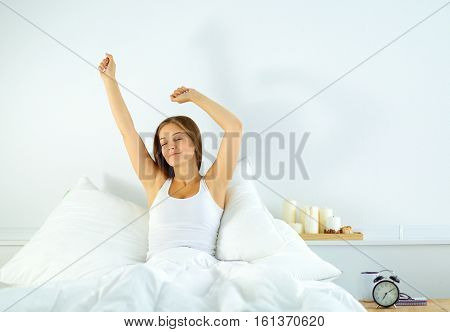 attractive young woman stretching in bed after waking up.