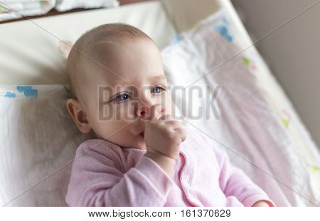 Portrait of a smiling baby laying on a changing table and suck his thumb