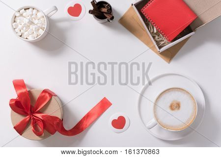 Day of love. Flat lay of different presents for the Valentines Day lying on the table decorated with paper hearts