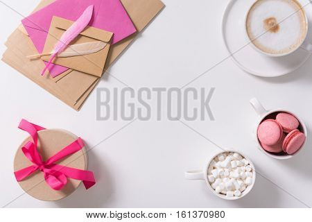 Confession of love. Pink feathers lying on the pile of paper envelopes near the gift box tied with pink ribbon