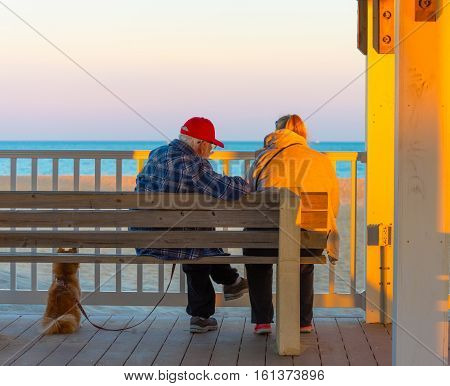 Manasquan NJ USA --November 17 2016. A couple with a dog sits a bench on the boardwalk watching the ocean in the waning hours of the afternoon. Editorial Use Only.