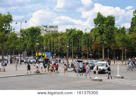 FRANCE PARIS - JULY 30 2014: Pedestrians crossing the road at a pedestrian crossing in the center of the Champs-Elysees.