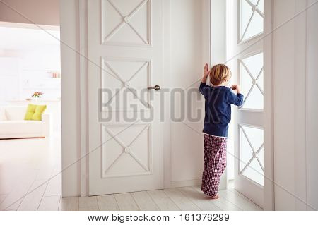 Curious Young Boy Looks Into The Ajar Door