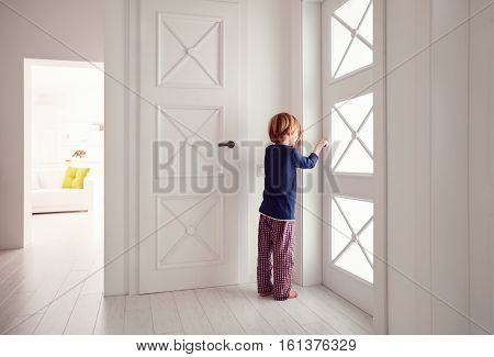 Young Boy Opens The Door At Home