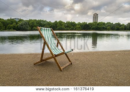 A lone deck chair early in the morning by the Serpentine Hyde Park London