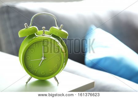 Green Alarm Clock On White Bedside Table