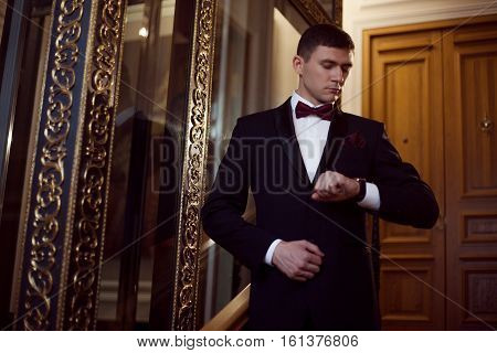 Handsome young man in a tuxedo looking at the camera. Clothing for the festive evening