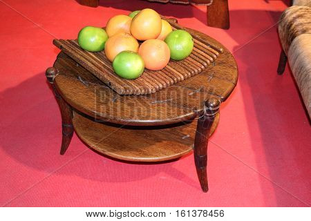 Coffee wooden table with a vase with fruit