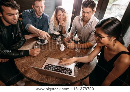 Diverse group of friends sitting together at cafe with man pointing at laptop. Five young people hanging out at a coffee shop