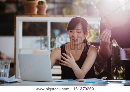 Shot of two young business colleagues looking at laptop. Businesspeople working together on laptop in office.