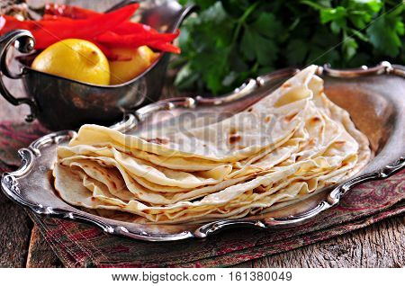 Homemade bread (pita, lavash bread) on old wooden background.