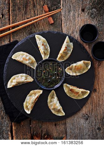 Fried asian dumpling (wonton) with chili sauce on the old wooden background.